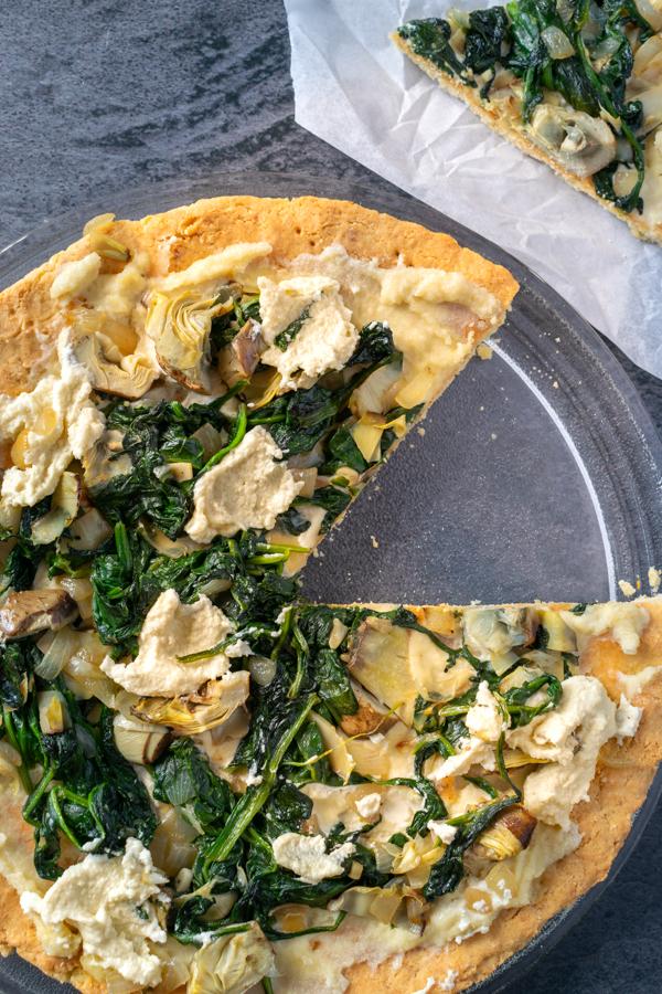 Pizza spinaci e carciofi paleo e chetogenica con spicchio tagliato immagine